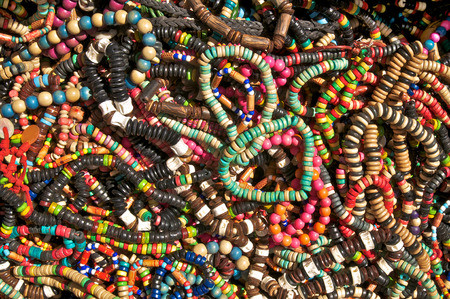 rummage: Necklets and bracelets of wooden beads unsorted on a rummage table; Special offer of fashion accessories