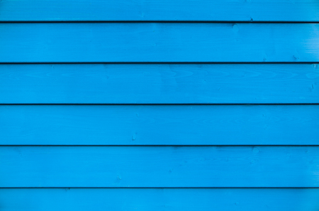 Wall of blue painted wooden slats; Blue painted wooden wall in landscape format for background