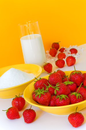 Ingredients for a tasty fruity strawberry milk shake; Yellow dishes with sugar and strawberries and a glass of milk against yellow background