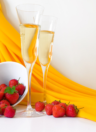 spirituous beverages: A little bit of luxury - champagne and strawberries; Two champagne glasses and a small dish with ripe strawberries