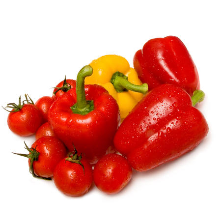 Washed red and yellow bell peppers ans ripe tomatoes on white background; Spicy and aromatic vegetables; Ingredients for salad