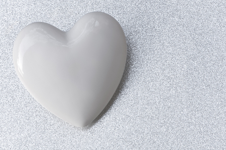 White glossy heart on silver background in landscape format; Silver wedding anniversary; 25 years of marriage