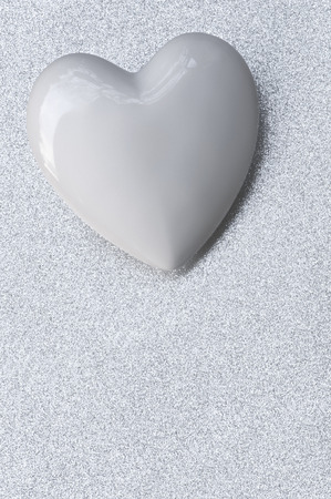 faithfulness: White porcelain heart on silver shining background; Silver wedding anniversary; 25 years in love; Declaration of love