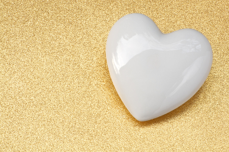 fidelidad: Glossy, white porcelain heart on golden glittery background; Golden Wedding; Wedding invitation card; Love note