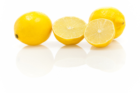 Lemons - whole fruit and halves on shiny white background with reflections; Citrus fruits; Cocktail ingredients; Stock Photo