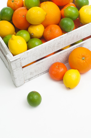 Wooden fruit crate filled with oranges, mandarines, lemons and limes on white background; Citrus fruits; Natural vitamin C for healty diet