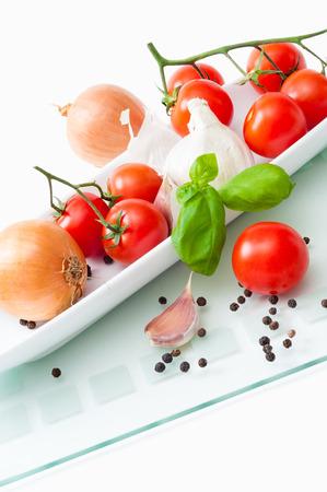 향미료, 토마토, 양파, 마늘, 후추 흰 접시; 지중해 음식을위한 향기로운 성분; 신선한 야채와 허브