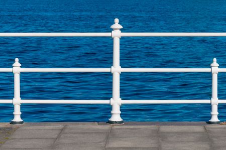 White laquered railing at ports border in front of deep blue sea; Maritine scenery; Walk on beach boardwalk