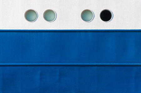 White and blue laquered side of a vessel with portholes; Varnished side of a ship for background; Seafaring Stock Photo
