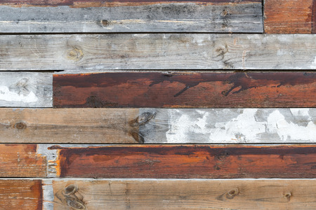 Grunge wooden wall for background; Old slats of wood knocked together; Renovation works; Wall of wooden planks in different colors; Provisional solution