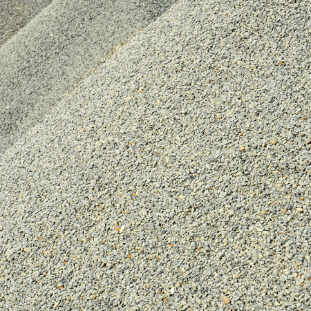 Pile of light gray gravel in close up for background or texture; Raw material for building industry; Gravel plans Stock Photo