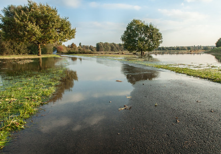 Impact of heavy rains; Flooded landscape in sunshine; Flood in autumn; Agricultural landscape with flooded fields Stock Photo