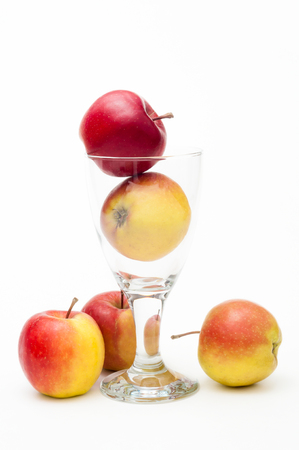 healthfulness: Crispy red-yellow apples Arranged with drinking glass against white background; Apple juice; Natural healthy fitness drink; Fruit juice