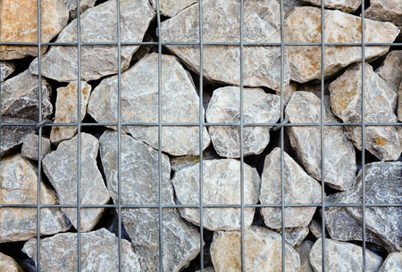 screened: Crushed natural stones in wire mesh basket close up for background; Stone wall for landscape gardening or slope stabilization; gabions