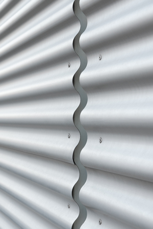 Corrugated, silver metal shetts in close up for background; Metal wall covering of modern architecture; Wavy metal surface