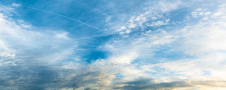 climatology: Panoramic view of overcast sky with cirrostratus clouds and condensation trails; Cloud formation at blue sky Stock Photo