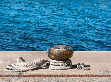 Rusty yellow bollard with worn out rope against blue sea; Empty mooring at the port