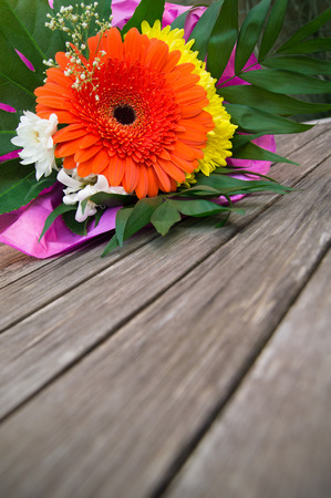 Small flower bouquet of orange gerberas and some white and yellow blossoms and green leaves on wooden planks; Mothers Day; Floral greeting card