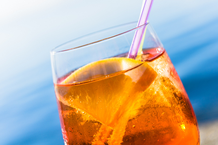 Refreshing summer drink; Transparent orange cocktail with ice cubes and drinking straw against blue background; Alcoholic cocktail; Summer holiday mood