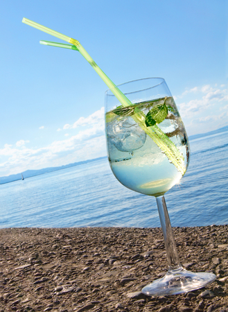 Cocktail with ice cubes, mint leaves and drinking straws against sea panorama; Summer drink; Relaxed holiday mood; Refreshing drink