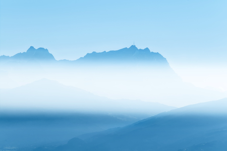 st gallen: View to the mountain Säntis in Switzerland; Panoramic view over mountain chain in blue morning mist Stock Photo