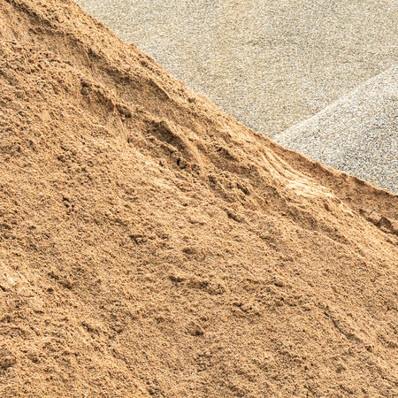 Piles of sand and fine gravel in close up for background; Raw material for road construction or building industry; Building materials trade