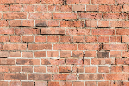 Old wall of red clay tiles for background or texture; Grunge masonry with broken red bricks and porous joints; Damaged red brick wall