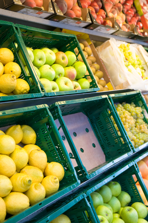 Fruit department at food retailing; Fresh fruits piled up in green plastic crates; Range of fruits - one variety in sold out