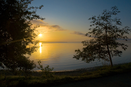 gloaming: Golden sunrise at Lake Constance in summer; Breathtaking start of a new day; Impression of sunup over calm water