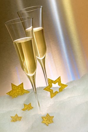 Two glasses of champagne in the snow, decorated with golden stars, against shining background; Consumption of alcohol; Celebration of solemn occasion Stock Photo