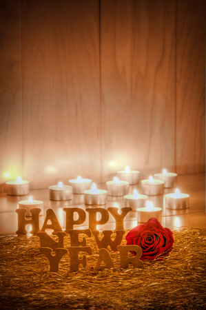 New Year's greetings; Happy New Year; Wooden letters on golden tinsel with a red rose and burning small candles against wooden background