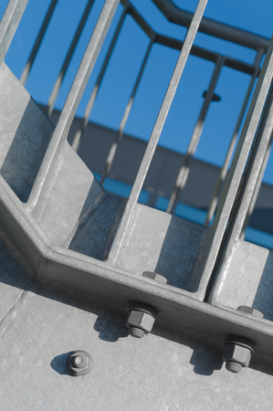 Steel construction with hexagonal nuts in sunlight; Handrail of modern external fire escape against blue background; Bolted steel connections