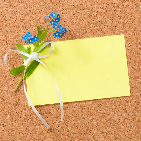 Yellow sticky note on cork board, decorated with forget-me-nots (myosotis) flowers and ribbon; Message with floral greetings; Pin board for memos or notes