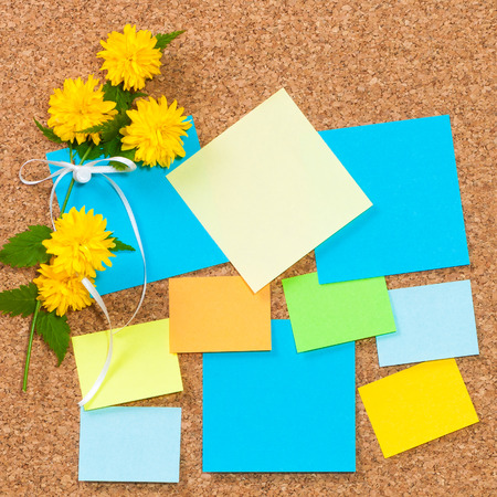 Sticky notes in different colors on cork board, decorated with yellow flowers and white ribbon; Pin board with blank sheets of paper; Write down your best ideas