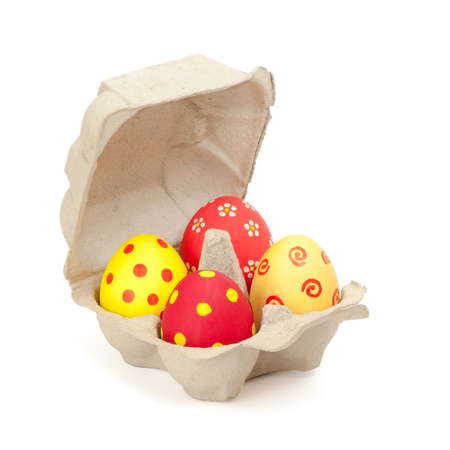Four hand painted Easter eggs in white egg carton against white background; Colored hens eggs in cardboard packaging; Happy Easter; Typical foodstuff at the easter time