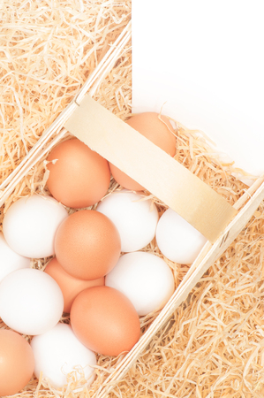 Brown and white chicken eggs in woodchip basket with wood wool and white sign with space for text; Poultry sector