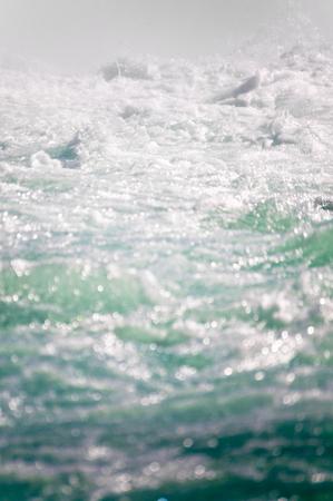 Wellenförmige Wasseroberfläche mit Schaum in der Nahaufnahme; Bewegtes Wasser; Grundelement des Lebens; Wasserversorgung