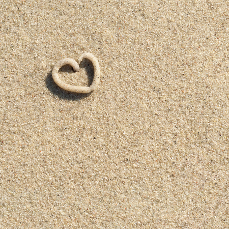 Small heart made of sand on sandy ground in sunlight, square format - top view; Symbol for love; Leaving of lugworm in the sand; Love letter; Holiday romance