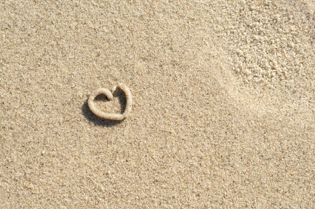 Small heart on sandy ground in landscape format - top view; Summer love; Symbol for love; Leaving of lugworm