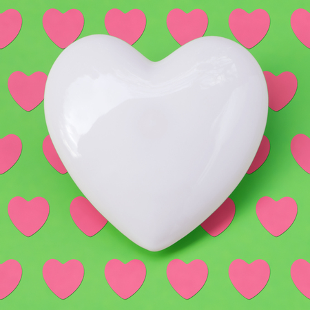 White porcelain heart on green background with small pink hearts; Valentine's Day; Mother's Day; Greeting card; Symbol of love