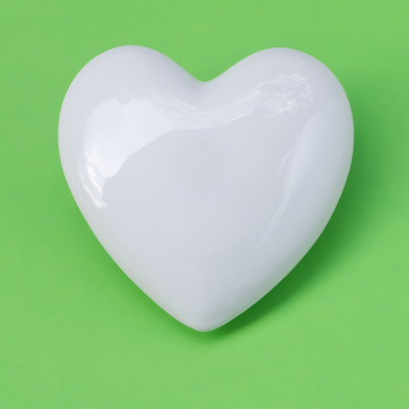Shiny white porcelain heart on green background; Symbol for love; Greetings for Mother's Day or Valentine's Day; With love Stockfoto