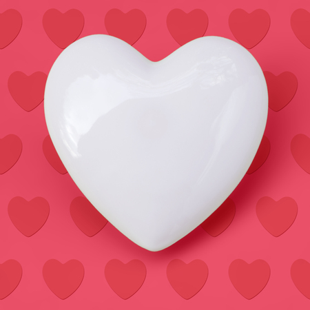 It comes from the heart; Shining white heart on rose background with little hearts; Motif for greeting card for Mother's Day or Valentines Day; Cordially