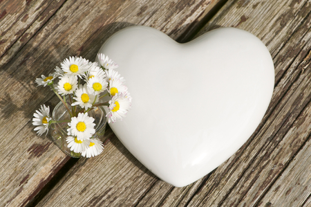 Porcelain heart and glass vase with some daisies arranged on wooden planks - top view, landscape format; Simple table decoration; Symbol for love and friendship; Greetings for Mother's Day; Wedding invitation