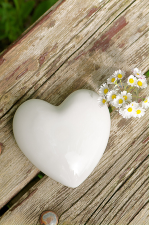 Shiny white porcelain heart and some daisies in small glass vase on old wooden plank - top view, upright format; Symbols for love and friendship; Greeting card for Valentine's Day; Rustic wedding invitation Standard-Bild
