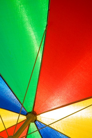 Sun umbrella in primary colors in closeup; Opened colorful sunshade - view from below; Sun protection
