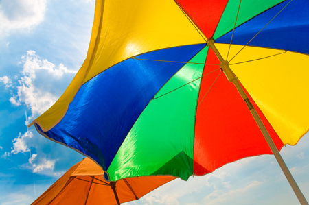 Opened colorful sun umbrellas against sunny blue sky with some clouds; Holiday greetings; Summer weather; Sunshade in basic colors