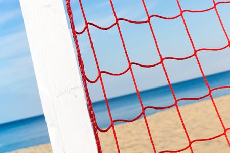 Red synthetic net fixed on white wooden post on the beach; Outdoor sports; Leisure activities on the beach; Beach soccer, Beach football