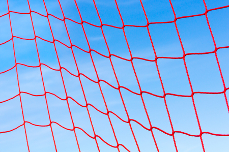 Red synthetic net against blue sky; Beach sports; Leisure activities outdoor