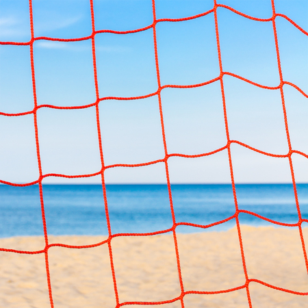 Red plastic net in closeup on sandy beach with blue ocean and cloudless sky; Beach sports; Leisure activities on the beach vacation