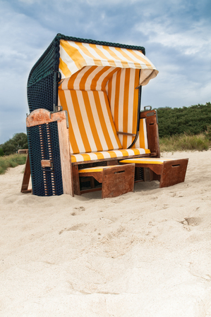Roofed wicker beach chair with blue wicker and yellow - white cover; German beach chair; Furniture for the beach; Relaxation in the sun
